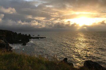 Sonne durchbricht Himmel am Meer