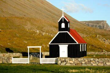 Kirche in schwarzem Holz und rotem Dach