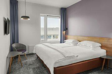 Doppelbett und fliederfarbene Wand